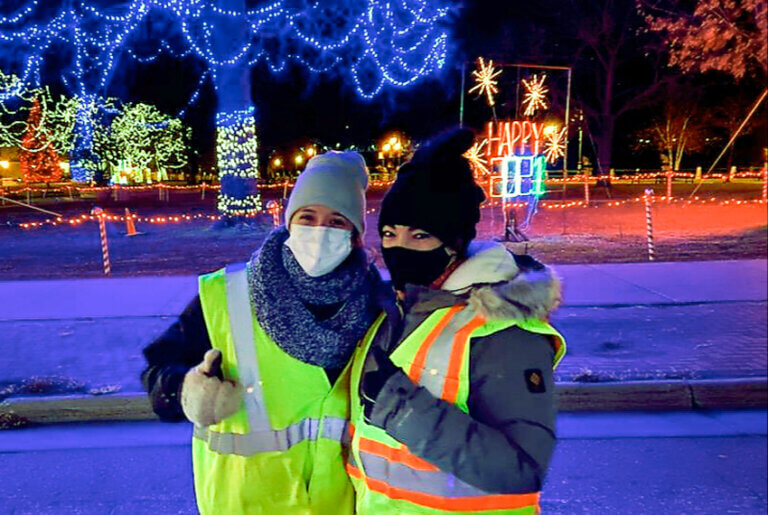 2 Orthodontists in safety jackets outside during a New Years celebration giving a thumbs up