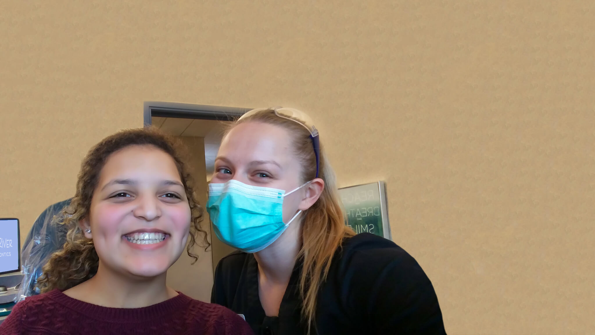 A doctor pictured next to her smiling patient with straight teeth