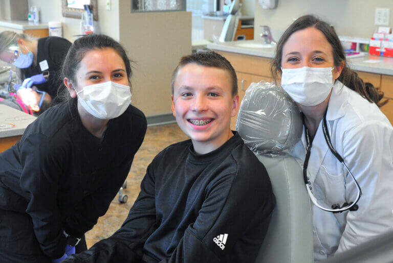 2 orthodontists pictured with a smiling patient with braces on