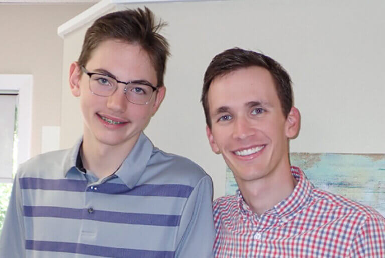 Orthodontist smiling with his patient who has braces