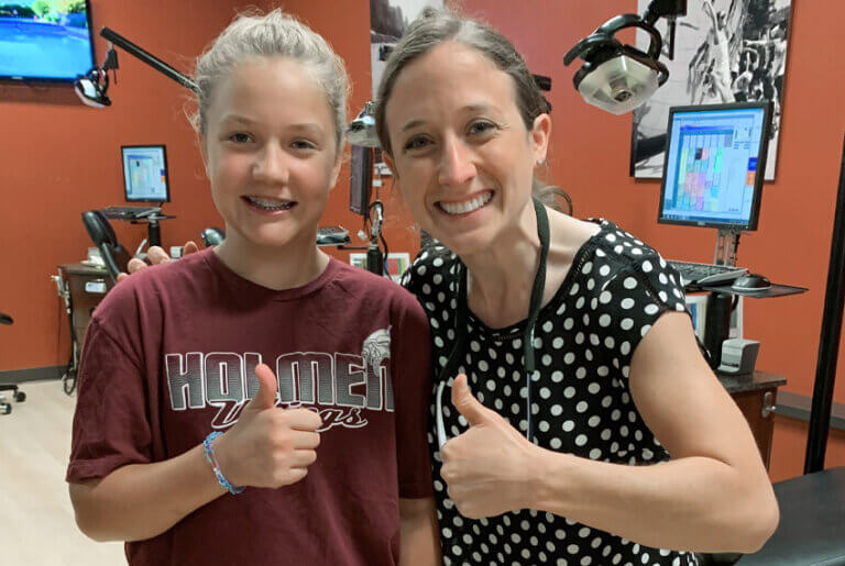 Orthodontist and her patient with braces giving a thumbs up
