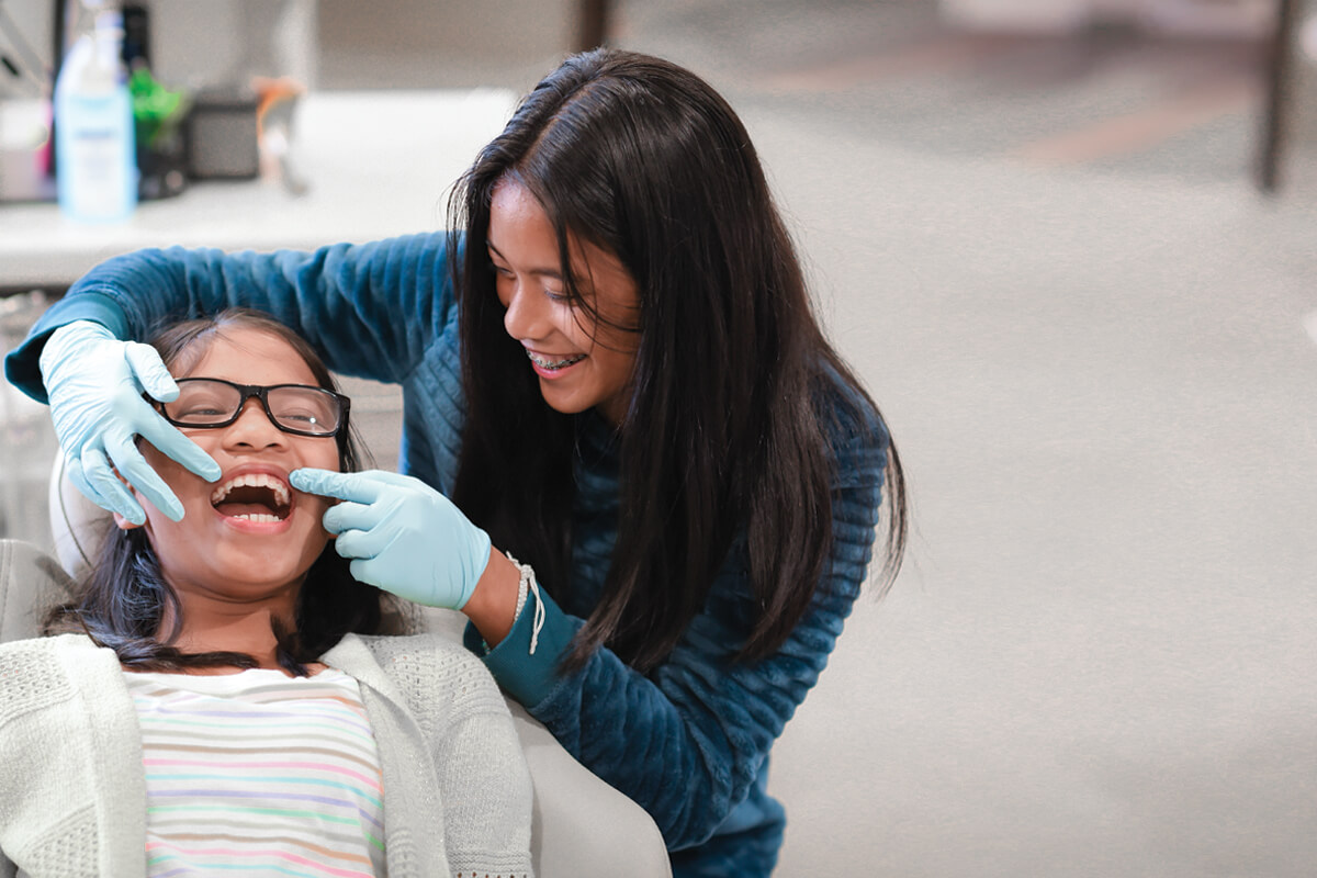 Doctor checking her patients teeth and smiling