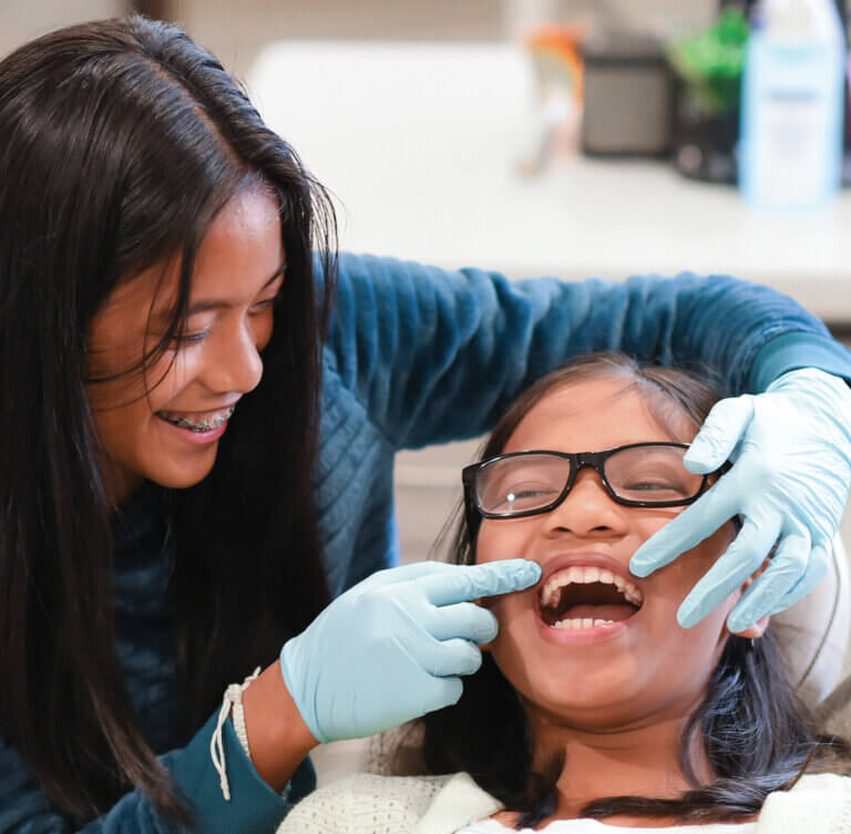 A smiling woman doctor inspecting her patient's teeth