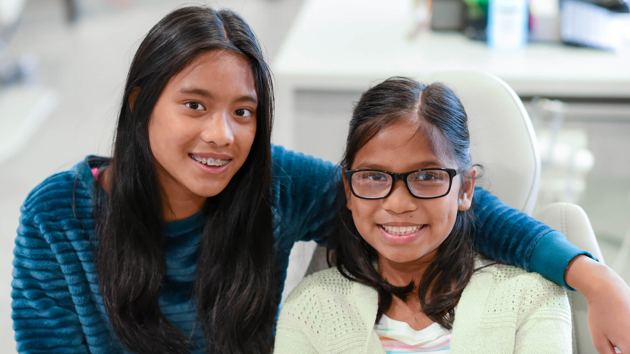 Girl with braces smiling with another girl who does not have braces