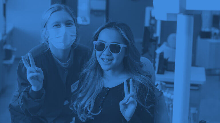 Doctor and her patient who has braces smiling and doing peace sign hand gestures