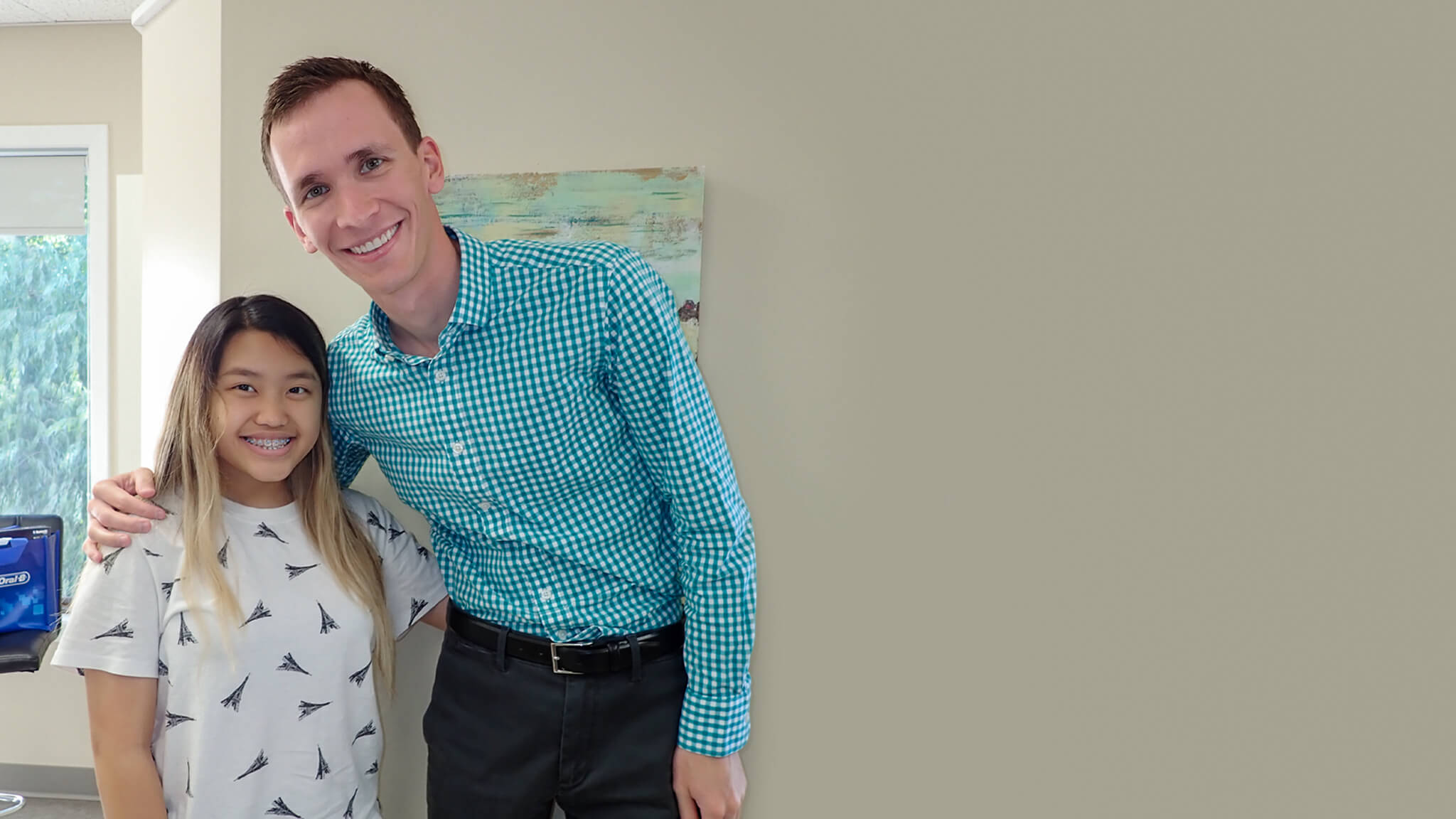 Doctor pictured next to smiling patient with straight teeth