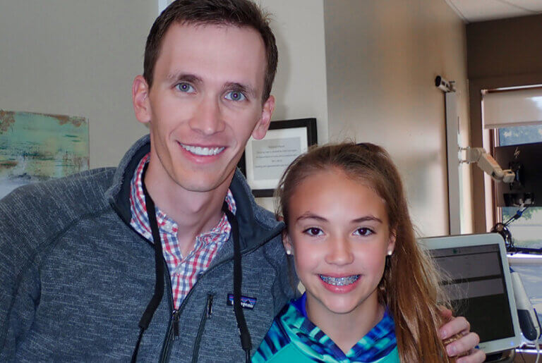 Orthodontist pictured with his patient who has braces