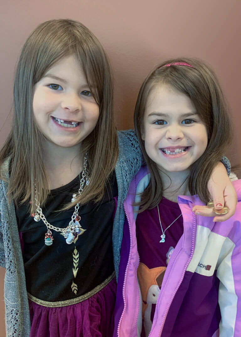 Two little girls smiling with missing teeth before orthodontic care