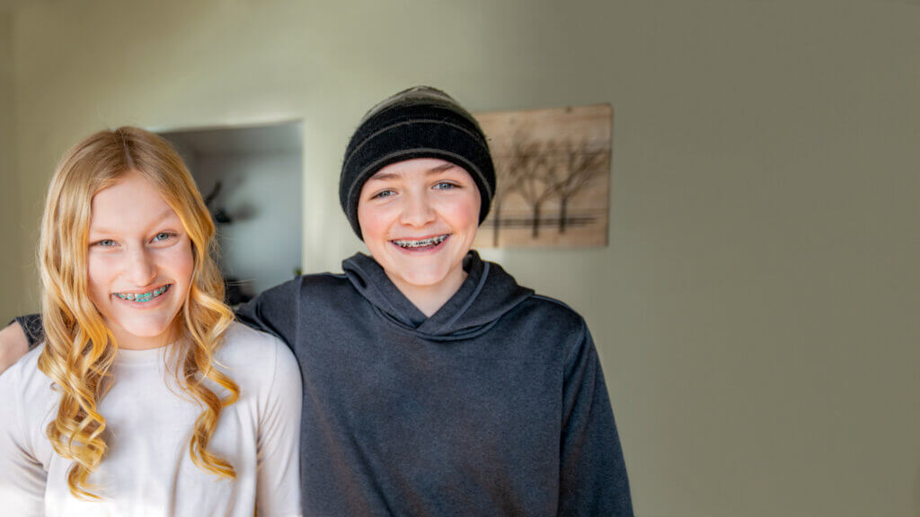 A girl and boy with braces smiling