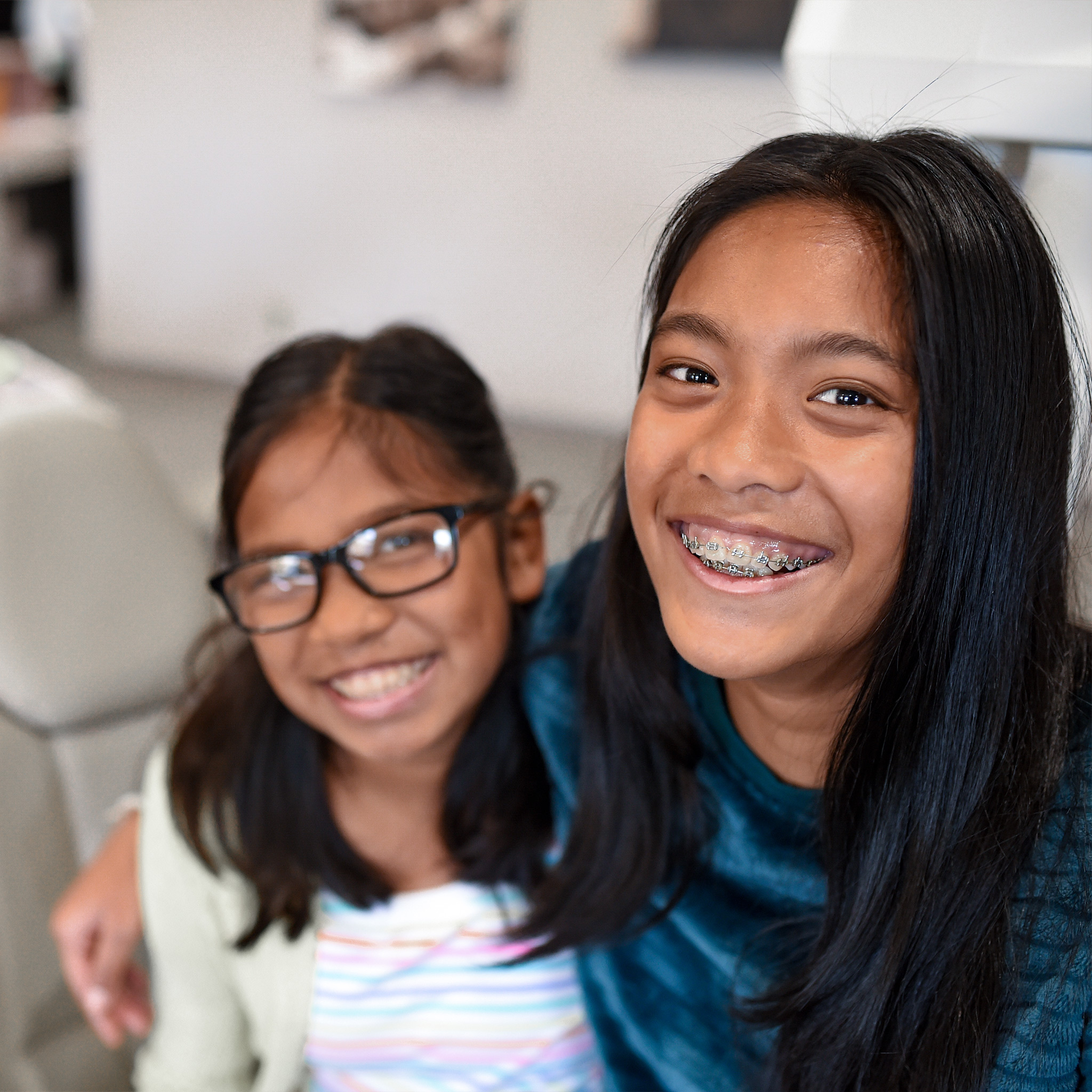 Young girl smiling with braces on sitting next to another young girl wearing glasses